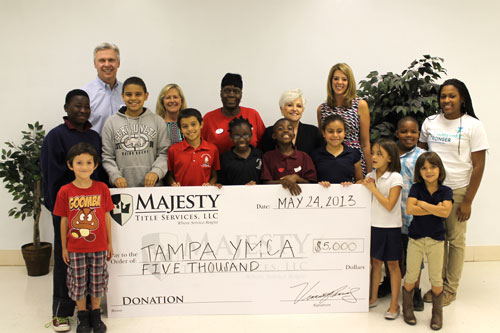 Photo Cutline: Staff and kids from the Central City Y's afterschool program join Tampa Y President & CEO Tom Looby, Majesty Title Services' Relationship Manager Kim Miller, Director of Operations Barbara Mendoza and Relationship Manager Erin Cassidy.